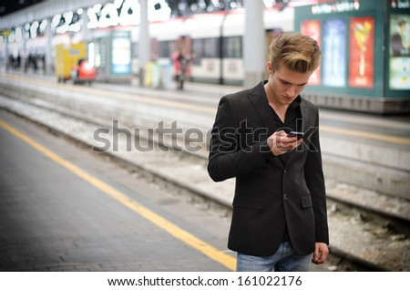 Attractive blond young man in train station using cellphone (mobile)