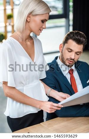 attractive blonde businesswoman holding folder near bearded coworker in office