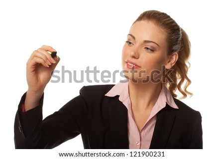Attractive blonde businesswoman holding up a felt tip pen in the air writing on blank copyspace or conceptual of a virtual screen