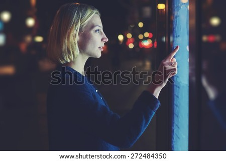 Attractive blonde female touching sensitive display with blue light while looking for touristic information with urban help technology system, futuristic device or smart bus station for self service #272484350