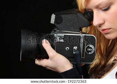 Attractive blonde girl photographing with medium format camera
