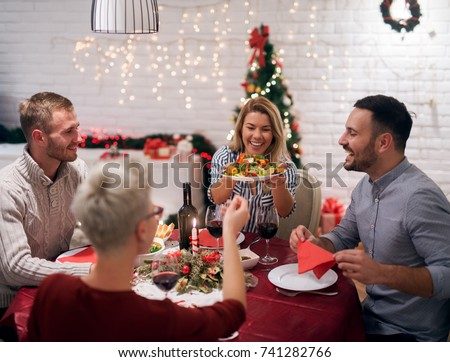Attractive blonde girl putting plate on the table while having Christmas lunch with boyfriend and friends,