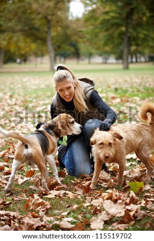 Attractive blonde girl stroking dogs in autumn park, smiling.