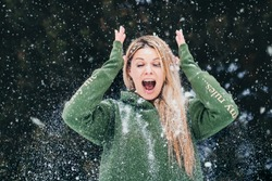 Attractive blonde has a Christmas mood in the frost having fun playing with snow