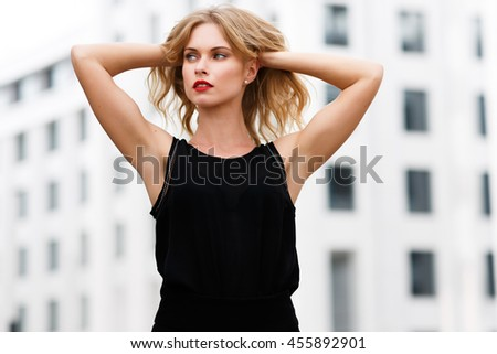 Attractive blonde in black blouse hair raises her hands