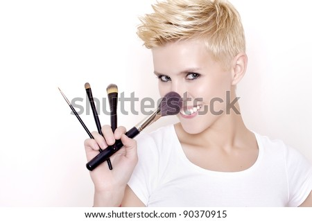 Attractive blonde Make-up artist holding brushes