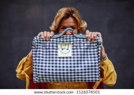 Attractive blonde stylish blonde caucasian senior woman standing outdoors in front of wall and holding bag with sticker note with smiley face on it.