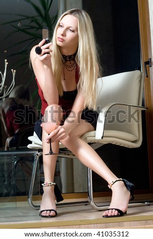 Attractive blonde with a glass of cocktail sending sms