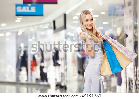 Attractive blonde with bags and a credit card in shop