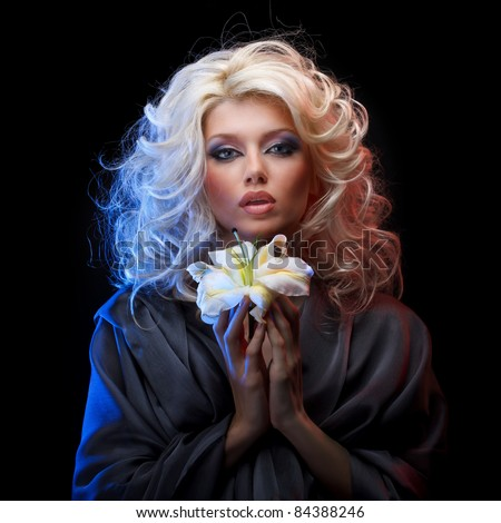 Attractive blonde with blue eyes wearing gray silk dress holding white lily by both hands on black background