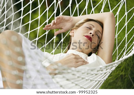 Attractive blonde woman laying down on a white hammock, sleeping and wearing red lipstick.