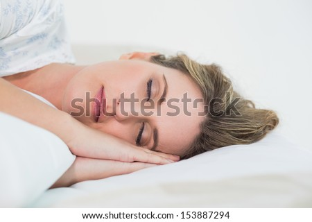 Attractive blonde woman sleeping in cosy bed - stock photo