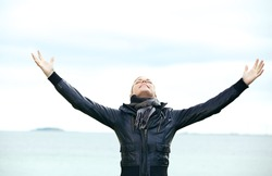 Attractive blonde woman standing rejoicing with her arms outspread and her head tilted back looking at the skies