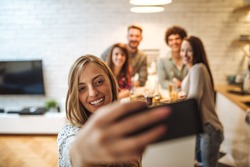 Attractive blonde woman taking a photo with friends in the kitchen while they're eating junk food and drinking beer.