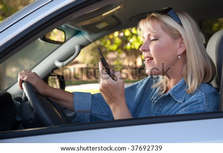 Attractive Blonde Woman Text Messaging on Her Cell Phone While Driving.