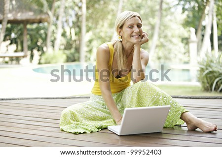 Attractive blonde woman using a laptop computer while sitting down on a wooden deck in a tropical garden.