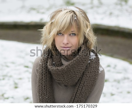 Stock Photo Attractive blonde young woman with wool scarf, snow around her