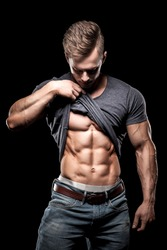 Attractive bodybuilder showing perfect abdominal muscles. Young guy shows abs. Sportsman shows six packs.