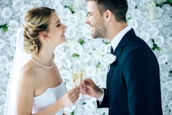 attractive bride and handsome bridegroom smiling and clinking with champagne glasses