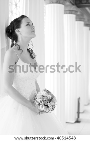 Attractive bride is holding a wedding bouquet and looking up