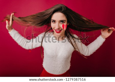 Stock Photo Attractive brown-haired woman in white sweater enjoying photoshoot in valentine's day. Romantic brunette girl with long hairstyle smiling on claret background.