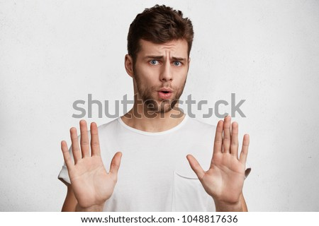 Attractive brunet male shows refusal gesture, doesn`t want to participate in meeting, says: It`s not for me, leave me in piece, has angry expression, poses against white concrete studio background #1048817636
