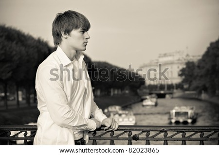 Attractive brunet young man on the bridge, sepia toned