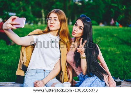 Attractive brunette and blonde female friends in casual stylish wear posing for selfie using mobile phone camera, hipster girls making picture for share in blog resting on free time in park