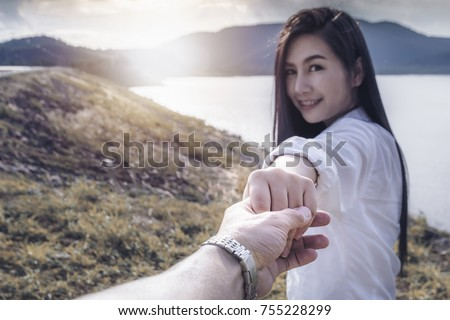 Attractive brunette asian girl holding boyfriend hands walk along the hillside