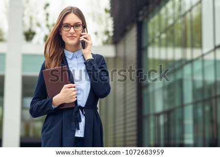 Attractive brunette businesswoman talking on mobile phone with client. Сток-фото ©