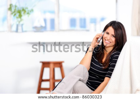 Attractive brunette chatting on the telephone at home