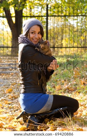 Attractive brunette chick and a kitten in the park at warm autumn day