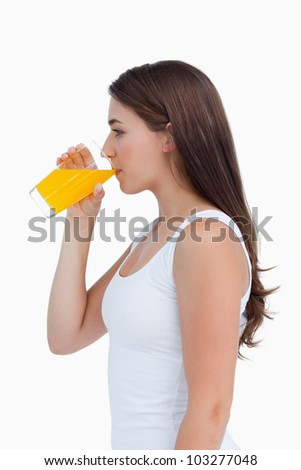 Attractive brunette drinking an orange juice against a white background