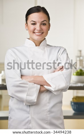 Attractive brunette, female chef smiling at the camera with her arms crossed. Vertical
