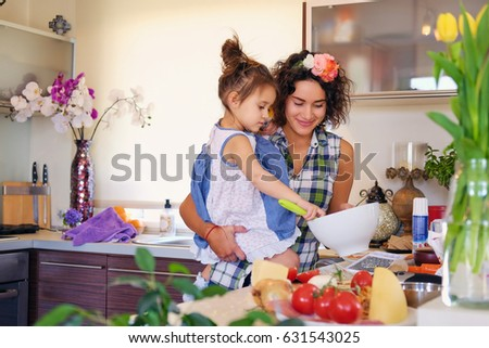 Attractive brunette female with curly hair and her cute little daughter cooking food in a home kitchen.