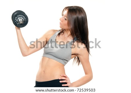 Attractive brunette fitness woman instructor on diet with perfect athletic body and abs working out with pink mini weights dumbbells in gym isolated on a white background