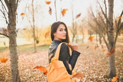 Attractive brunette girl with orange backpack turns around in an autumn park - fall colors