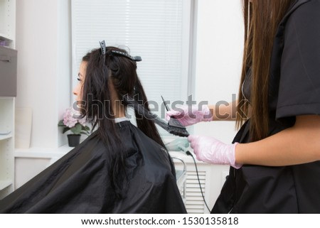 Attractive brunette hairdresser thoroughly dyeing hair of female client while she is sitting in beauty salon
