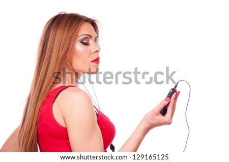Attractive brunette holding mobile cell phone and listen to music in earphones, isolated on white