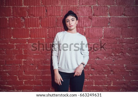 Attractive brunette in a gray sweatshirt stands on a red brick wall background. Mock-up.