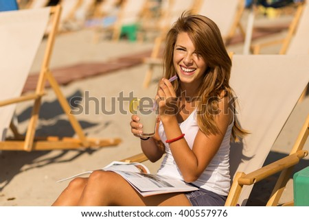 Attractive brunette lying on a sunbed on a beach, drinking lemonade, reading a magazine and enjoying the sun