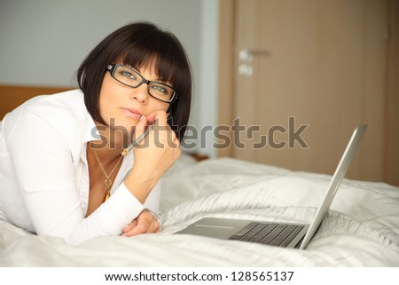 attractive brunette lying on bed with laptop and pen