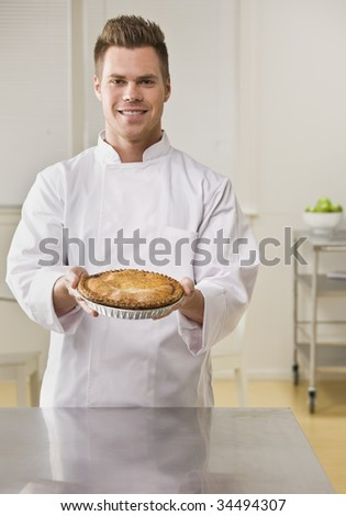 Attractive brunette male holding pie and smiling at camera. Vertical.
