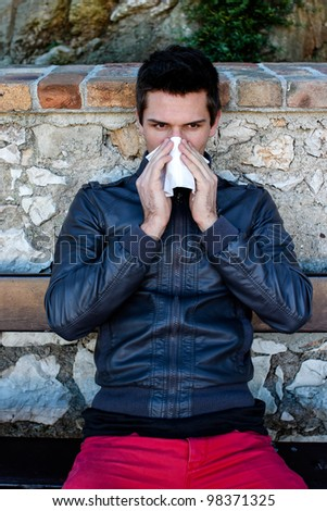 Attractive Brunette Man With Red Pants Blowing He's Nose While Sitting On A Bench In A Park