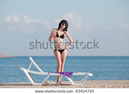 Attractive brunette on the beach. Young woman in black bikini posing on open air.