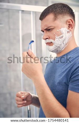 Attractive brunette surprised male observing razor for shaving his face n the morning Foto stock ©