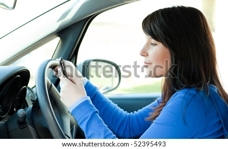 Attractive brunette teen girl using a mobile phone while driving