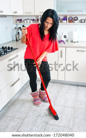 attractive brunette woman cleaning broken glass from the floor in the kitchen