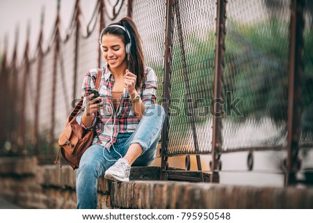 Attractive brunette woman enjoying free time outdoors with music.