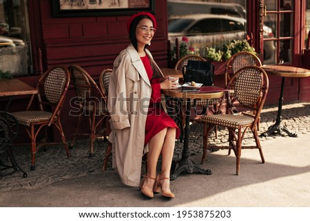 Attractive brunette woman in red dress, beige trench coat and beret smiles, sits in street cafe and enjoys coffee. Photo stock ©